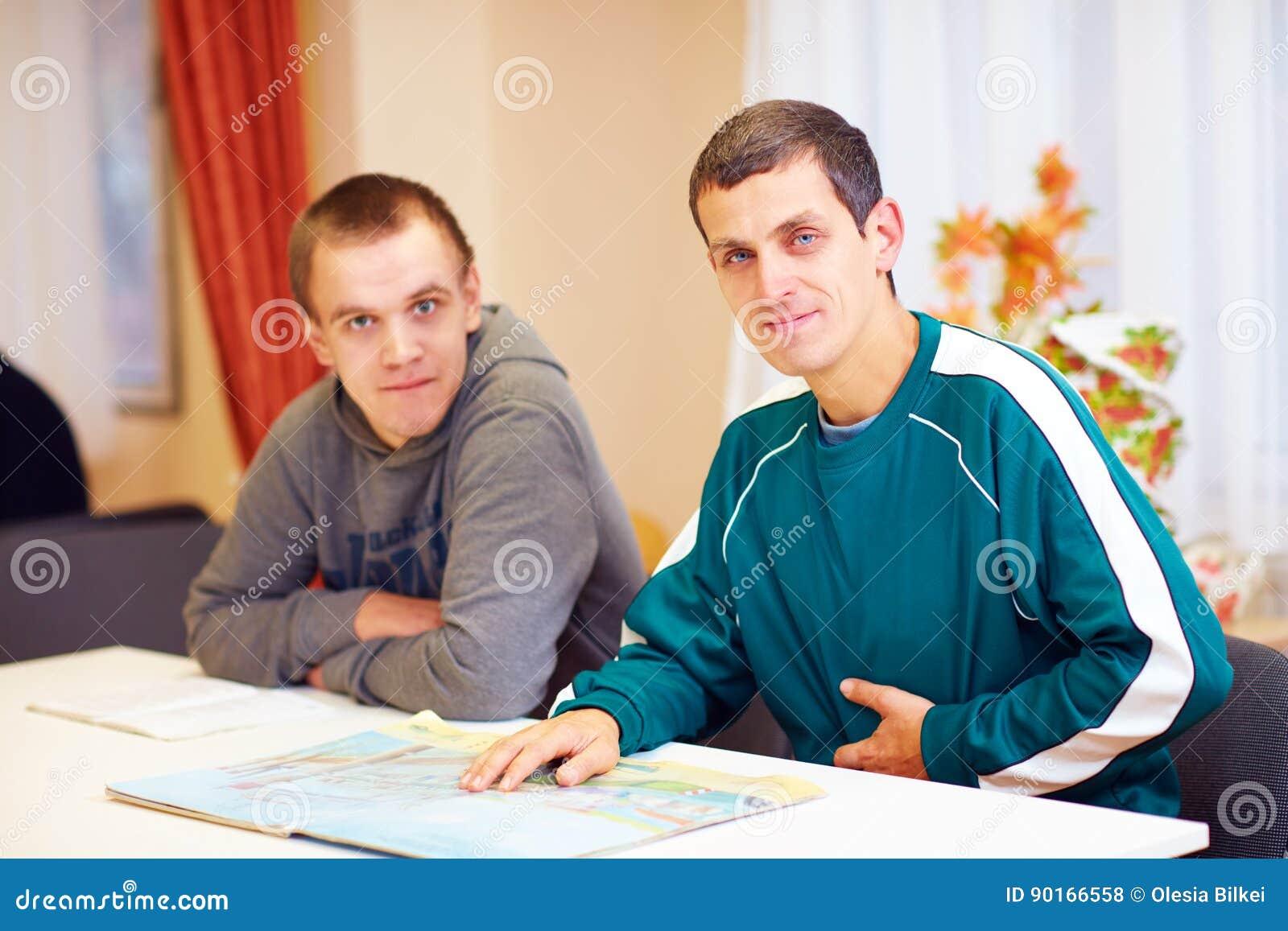 Vrolijke volwassen mensen met onbekwaamheidszitting bij het bureau in revalidatiecentrum