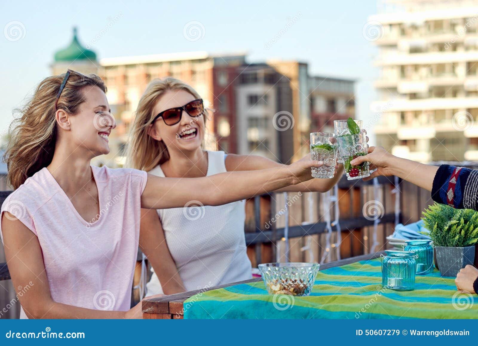 Vrolijke vrienden die cocktails drinken