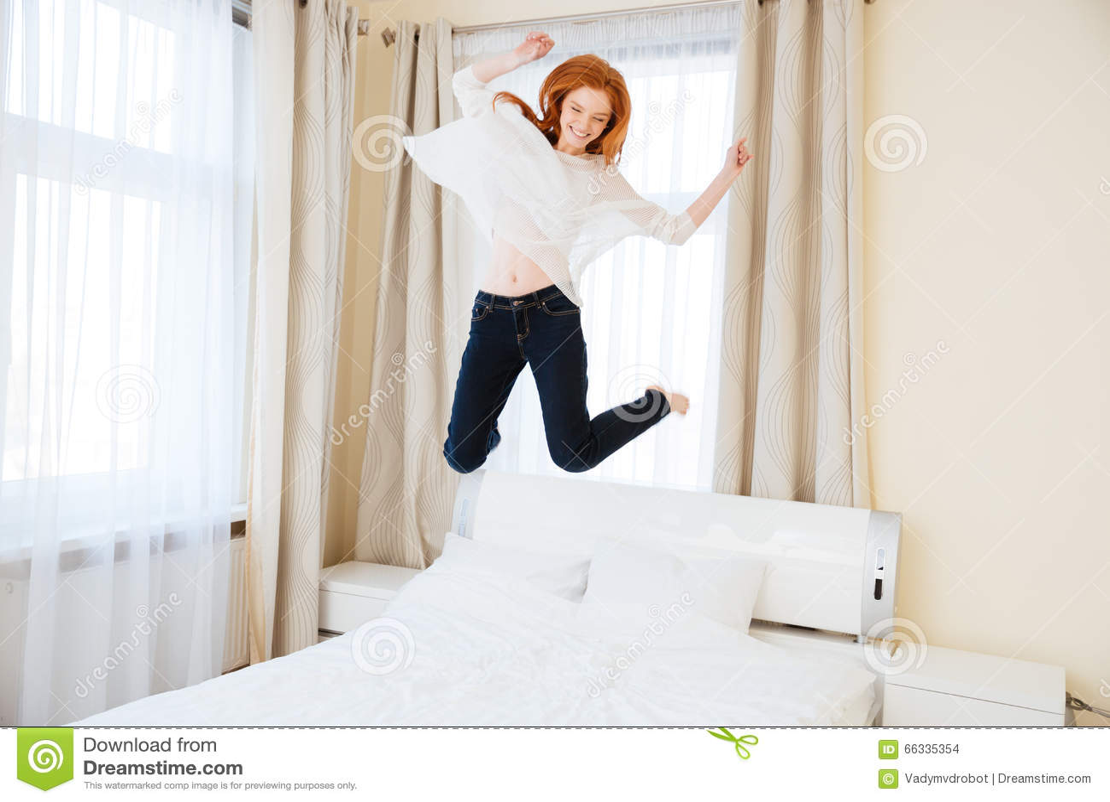 Vrolijke vrouw die op het bed springen