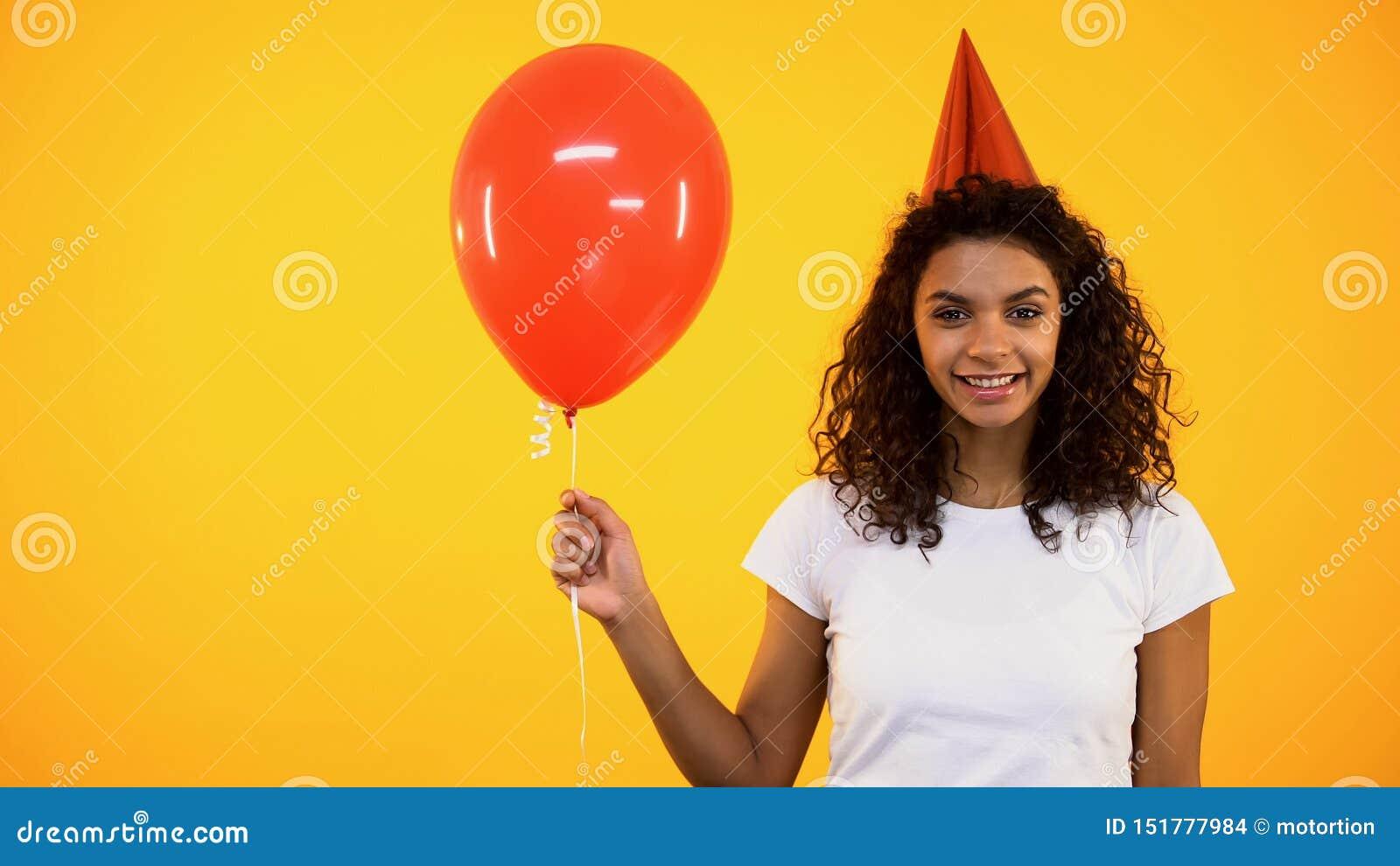 Vrolijke vrouwelijke rode ballon houden en tiener die, verjaardagsviering, pret glimlachen