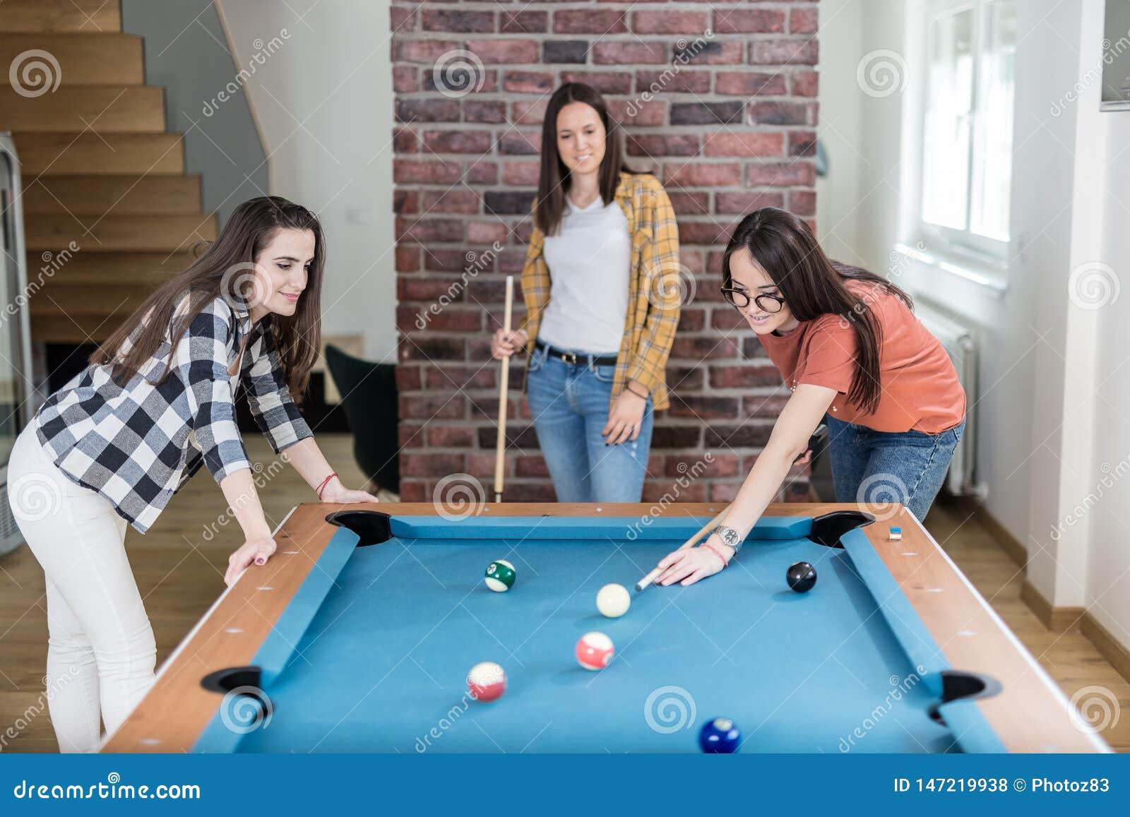 Vrolijke vrouwelijke vrienden die het biljartspel thuis spelen van de poollijst