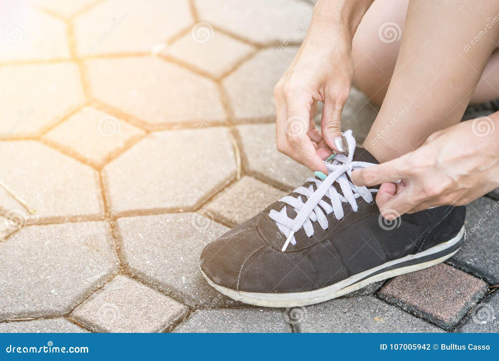 Vrouw bereid te lopen en bindende loopschoenen die worden