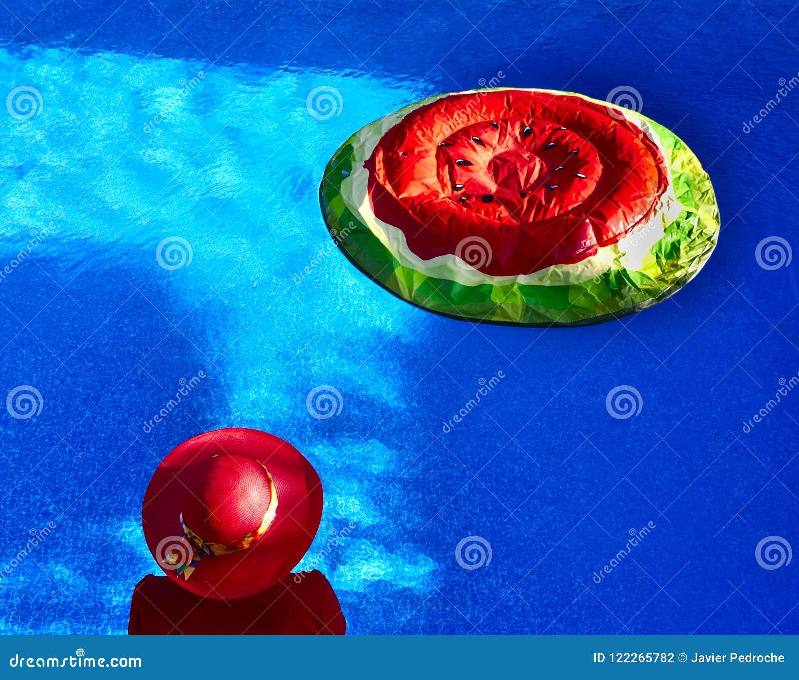 Vrouw bij de zwembad en watermeloenvlotter