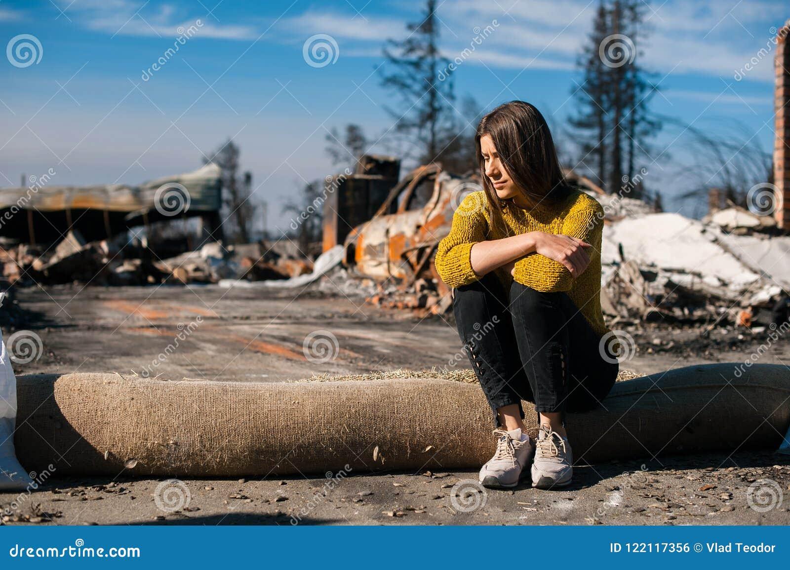 Vrouw bij gebrande geruïneerde huis en werf, na brandramp