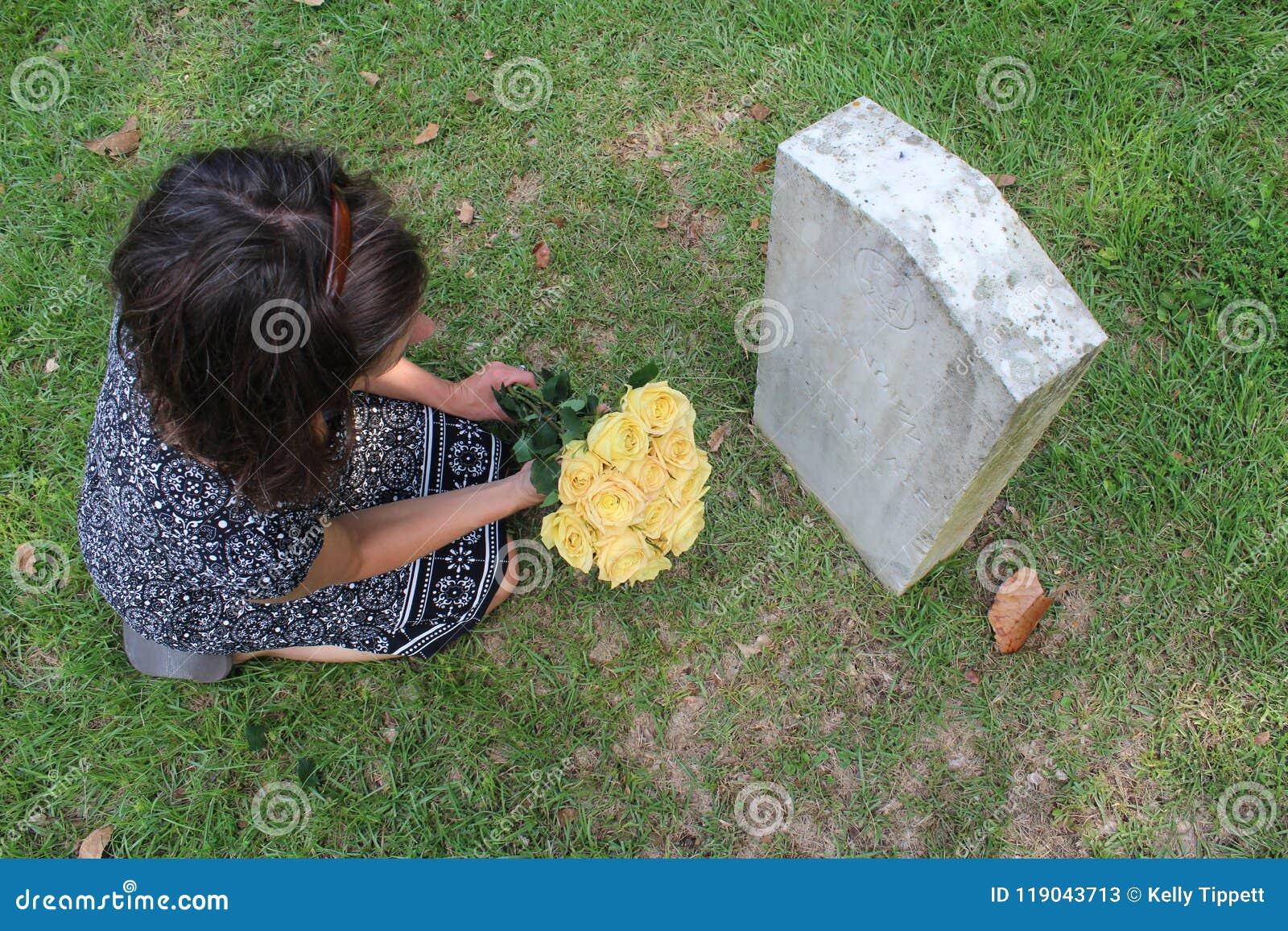 Vrouw bij Onbekend militair` s graf met gele bloemen