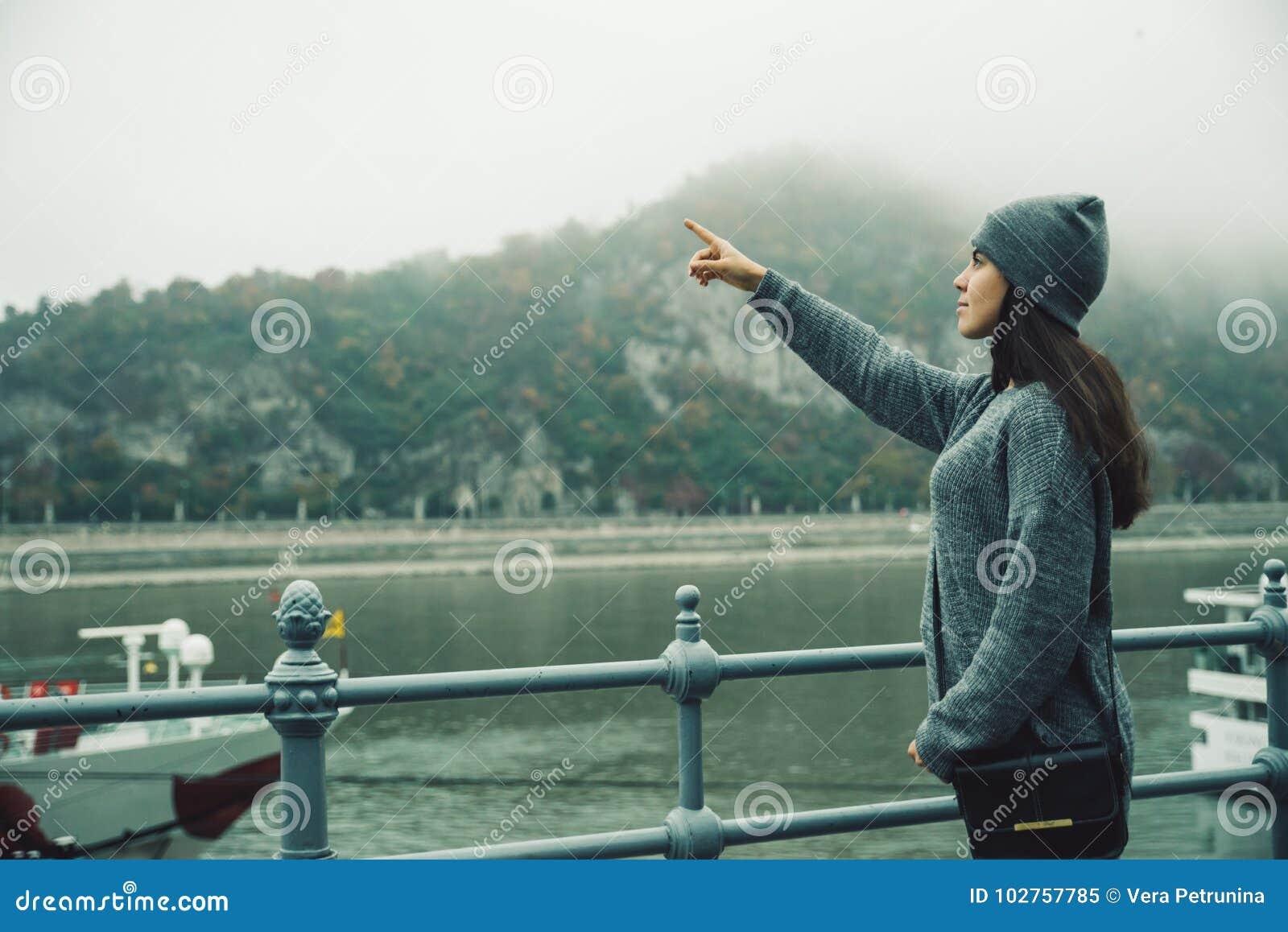 Vrouw bij stadsdok in mistige dag