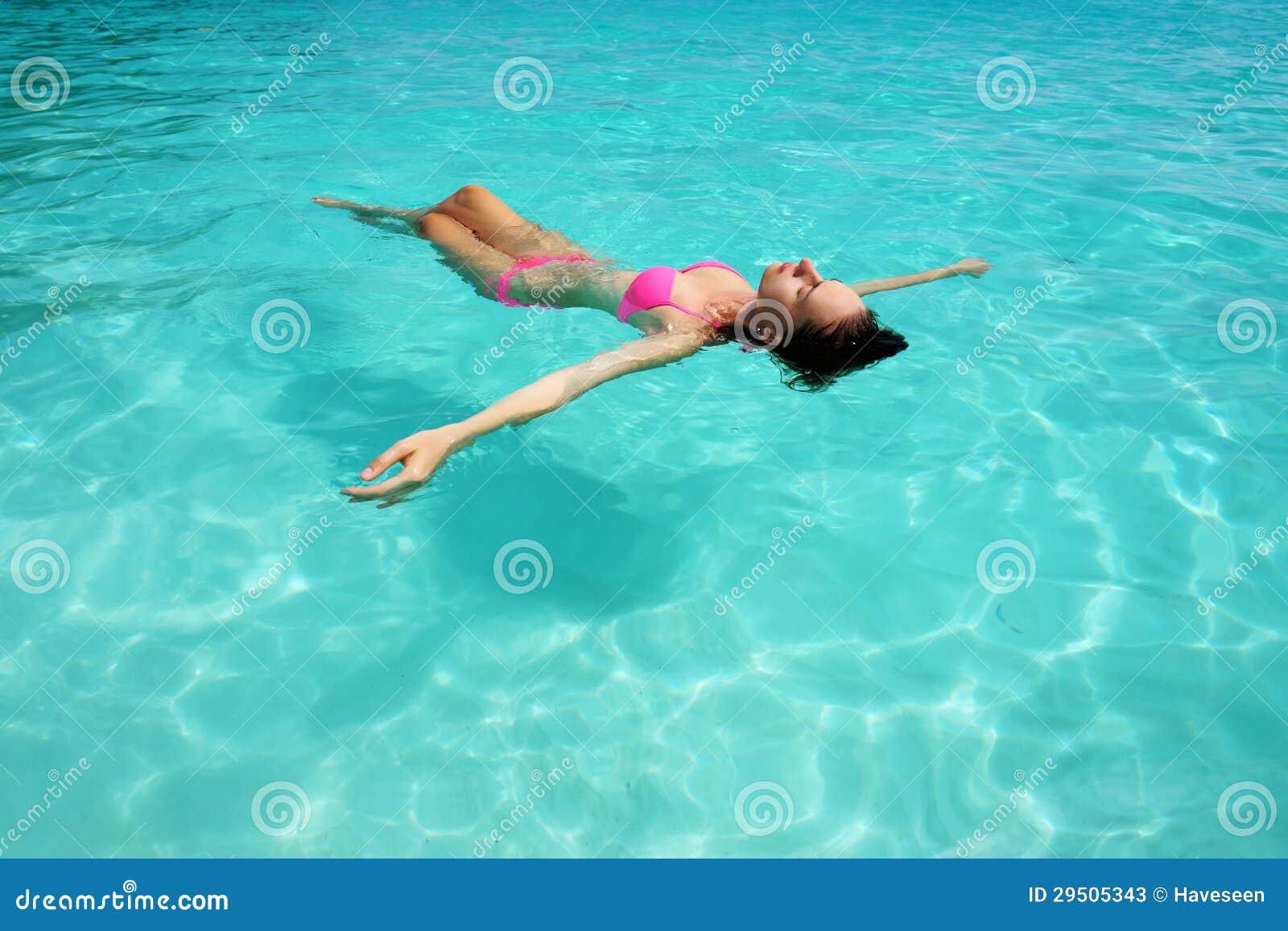 Vrouw in bikini die op water liggen