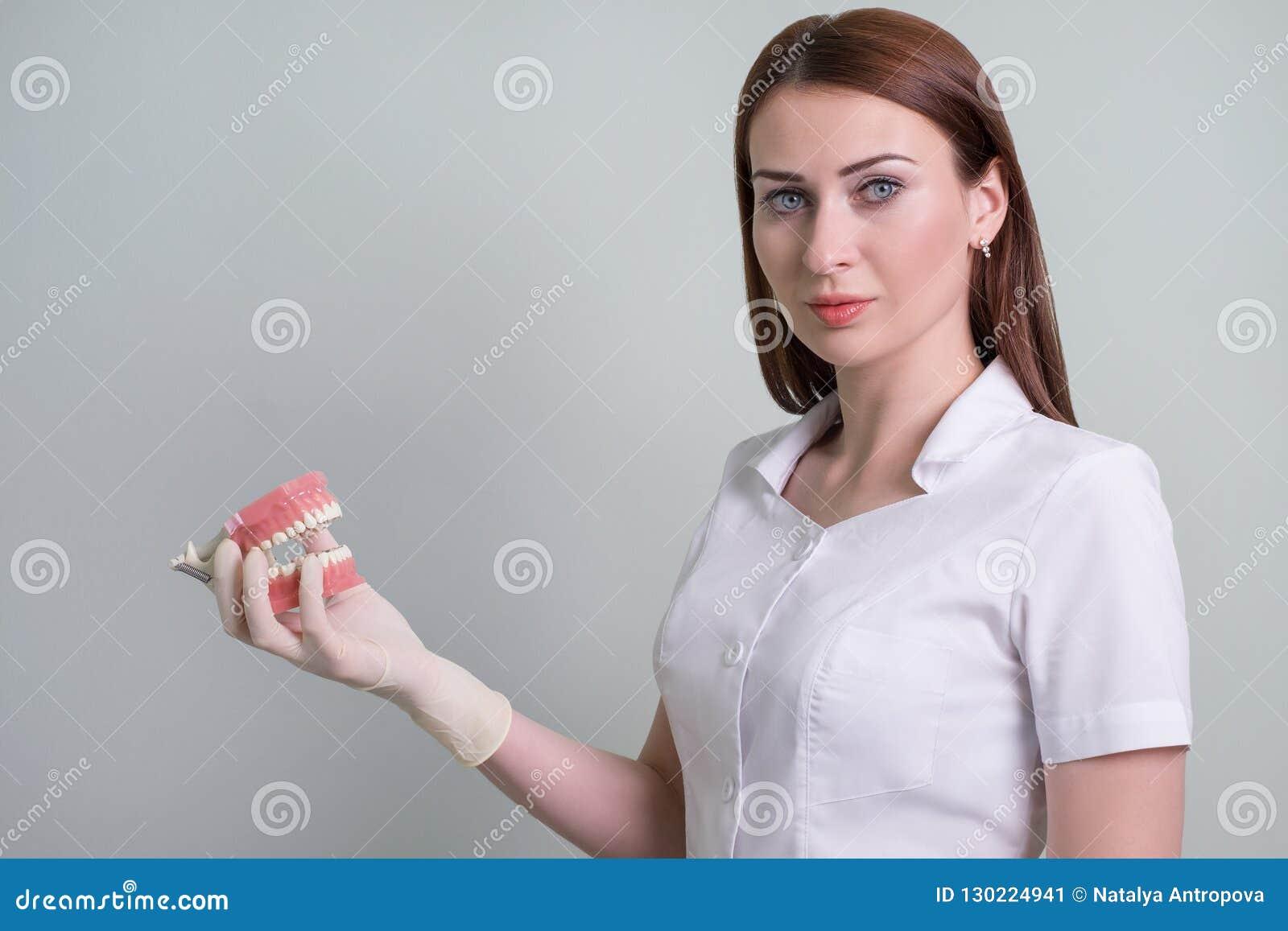 Vrouw de arts toont mondelinge hygiëne op de lay-out aan, tandheelkunde Ruimte voor tekst