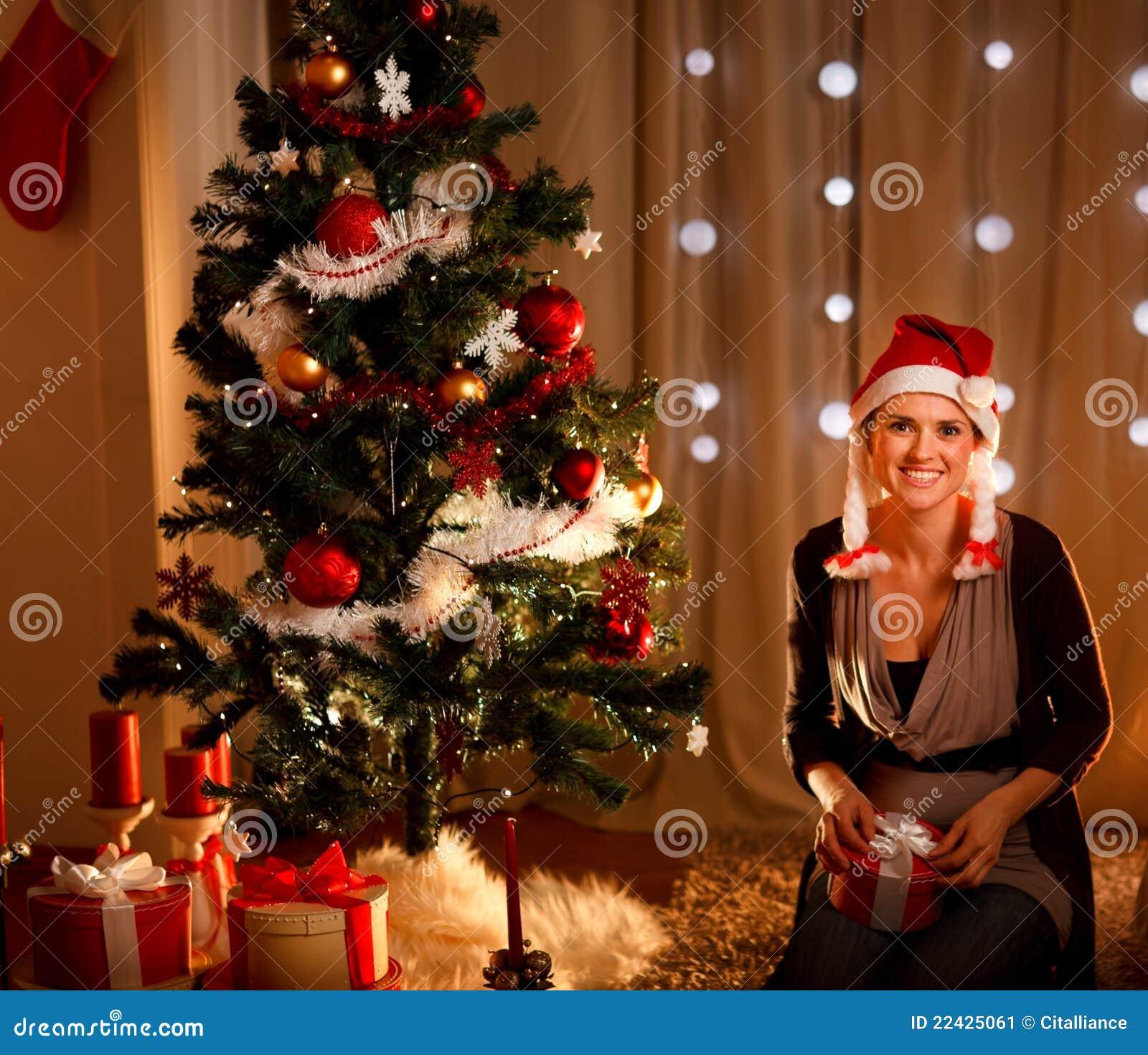 Vrouw dichtbij de holdingsgift van de Kerstboom