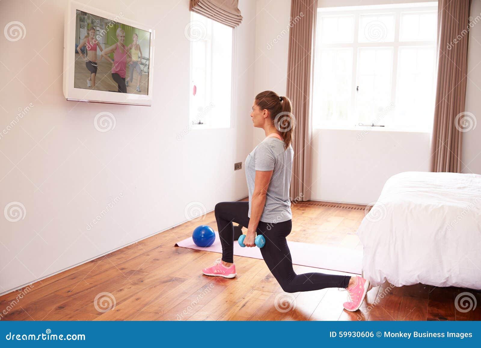 Tv In Slaapkamer : Vrouw die aan geschiktheid dvd op tv in slaapkamer uitwerken stock