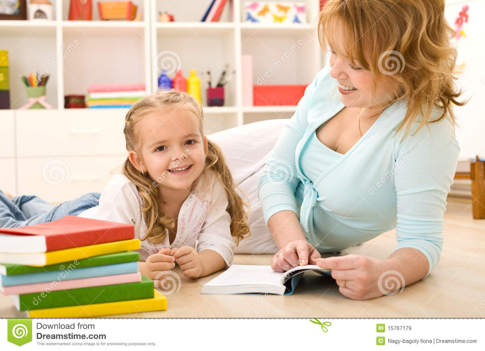 Vrouw die aan haar meisje leest