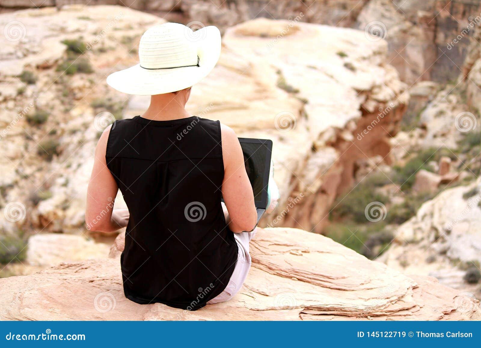Vrouw die aan laptop computer hoog op rotsen uitwerken