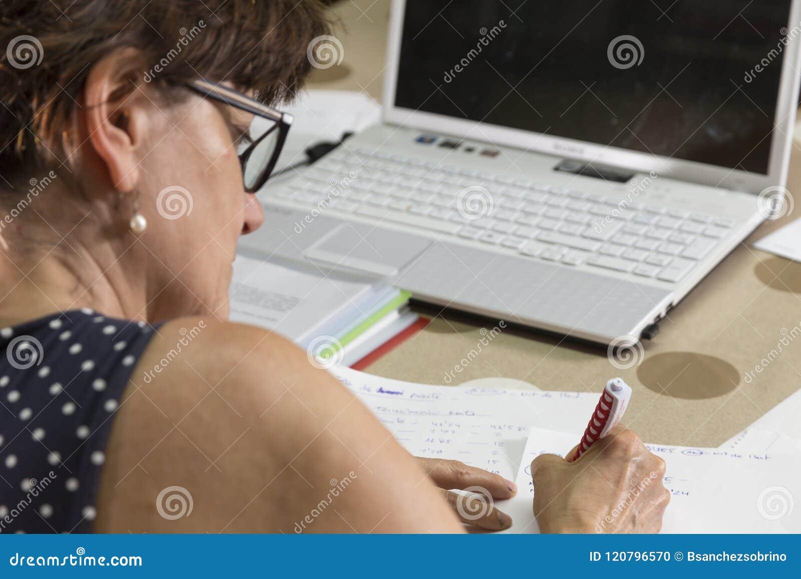Vrouw die aan manuscripten, omslagen en computerdocumenten werken