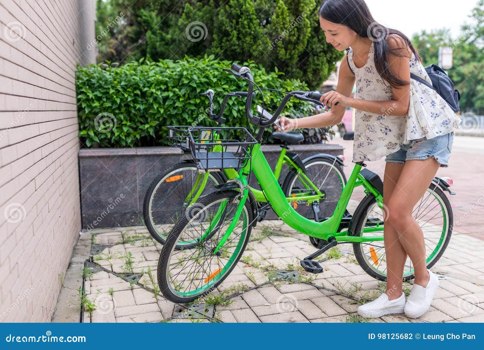 Vrouw die aandeelfiets in de stad met behulp van