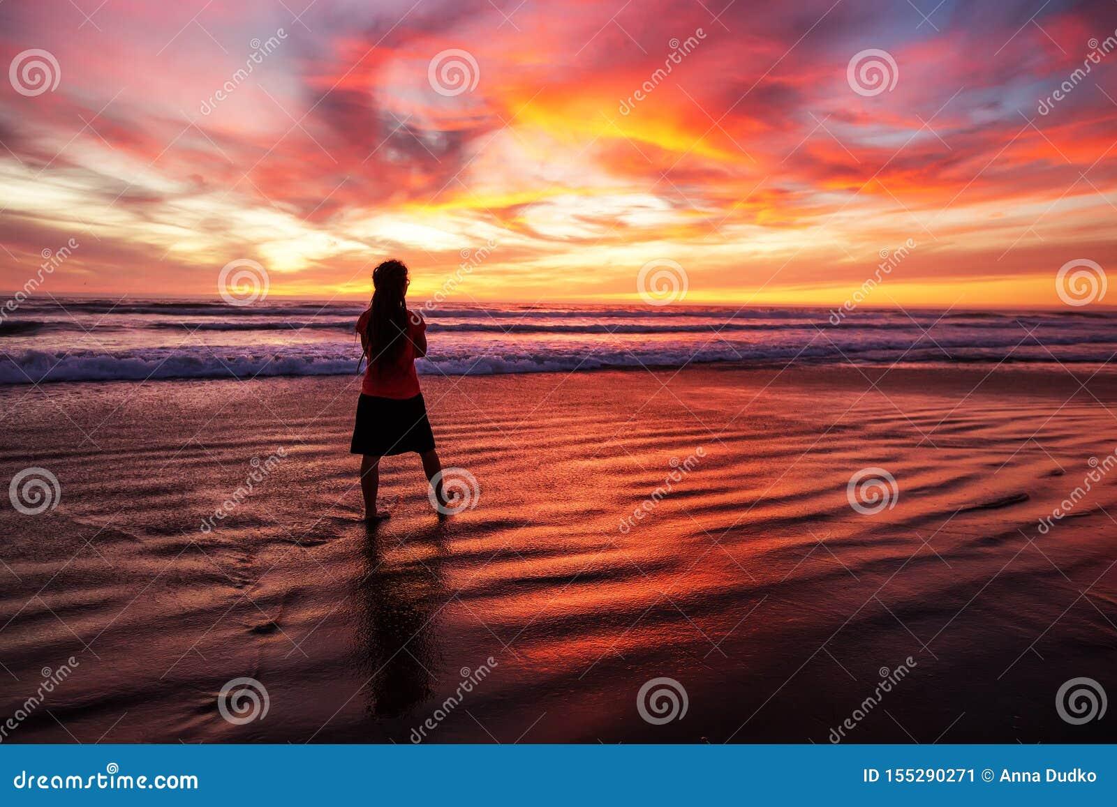 Vrouw die alleen op het strand in de zonsondergang lopen