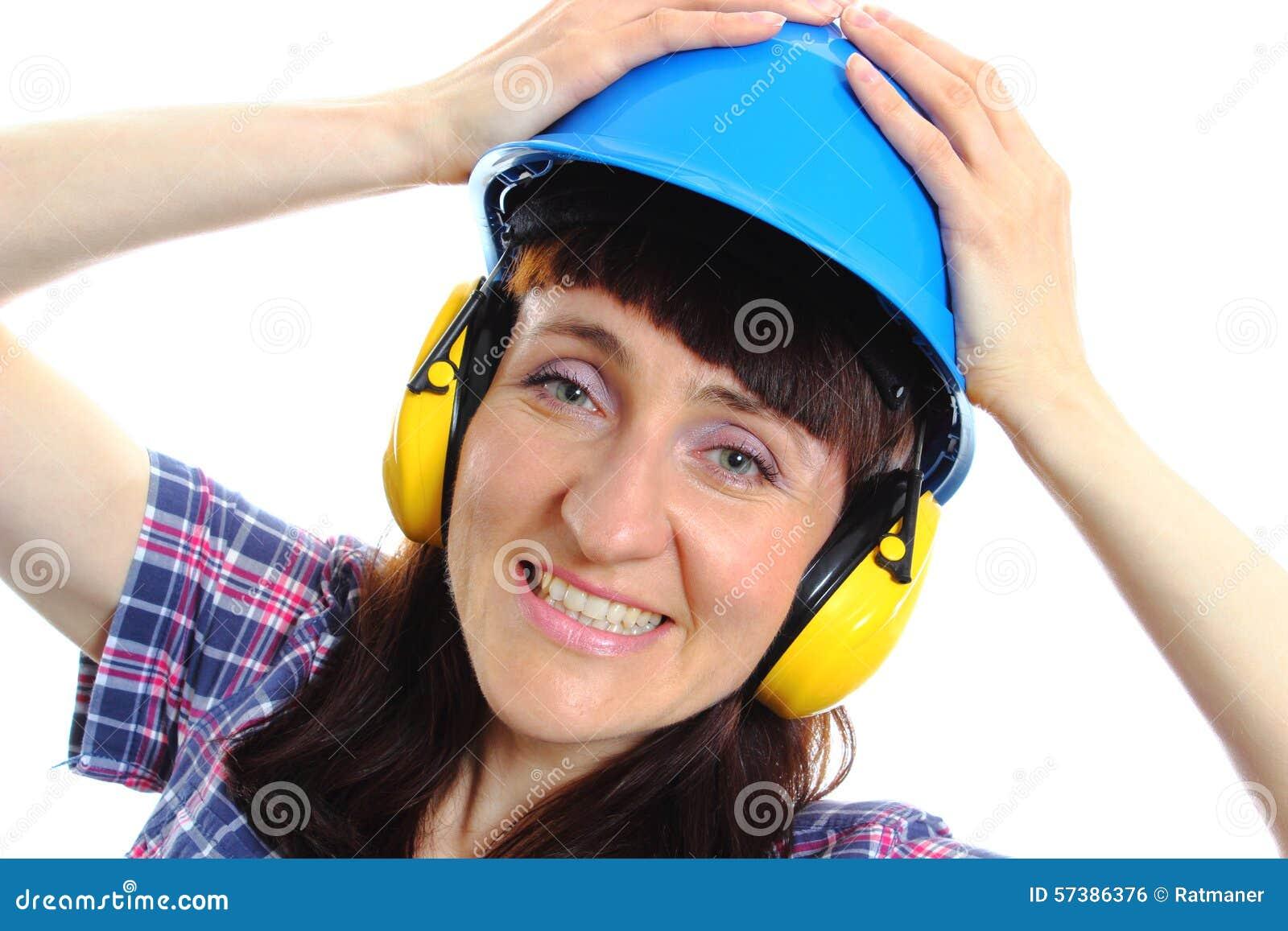 Vrouw die beschermende helm en hoofdtelefoons dragen