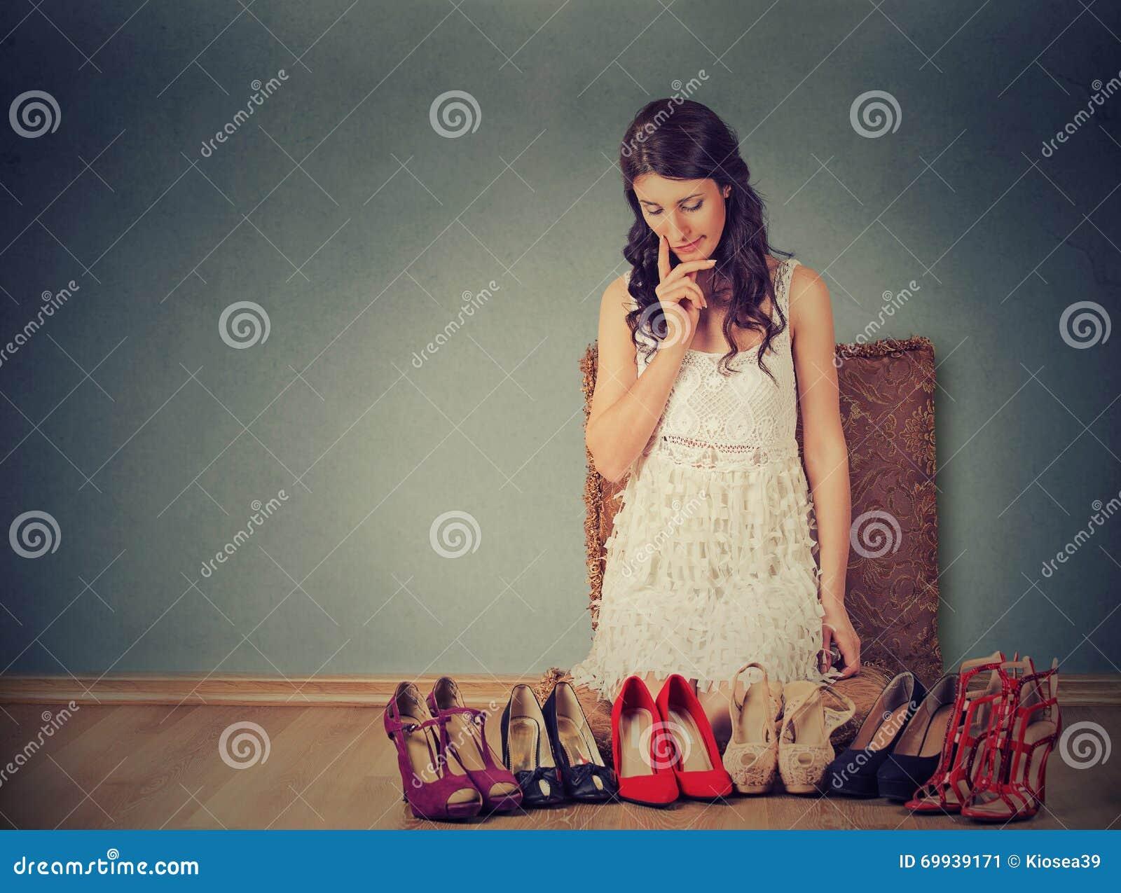 Vrouw die besluiten nemen die juist paar hoge hielschoenen plukken