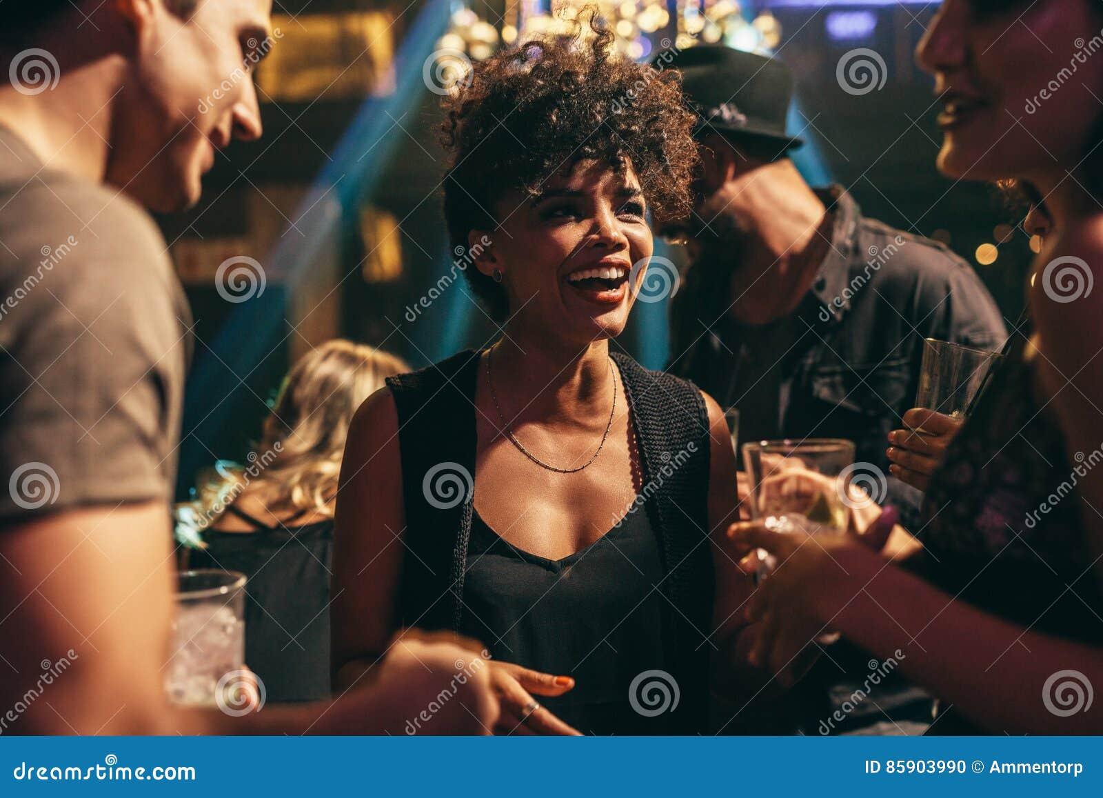 Vrouw die bij nachtclub met vrienden genieten van