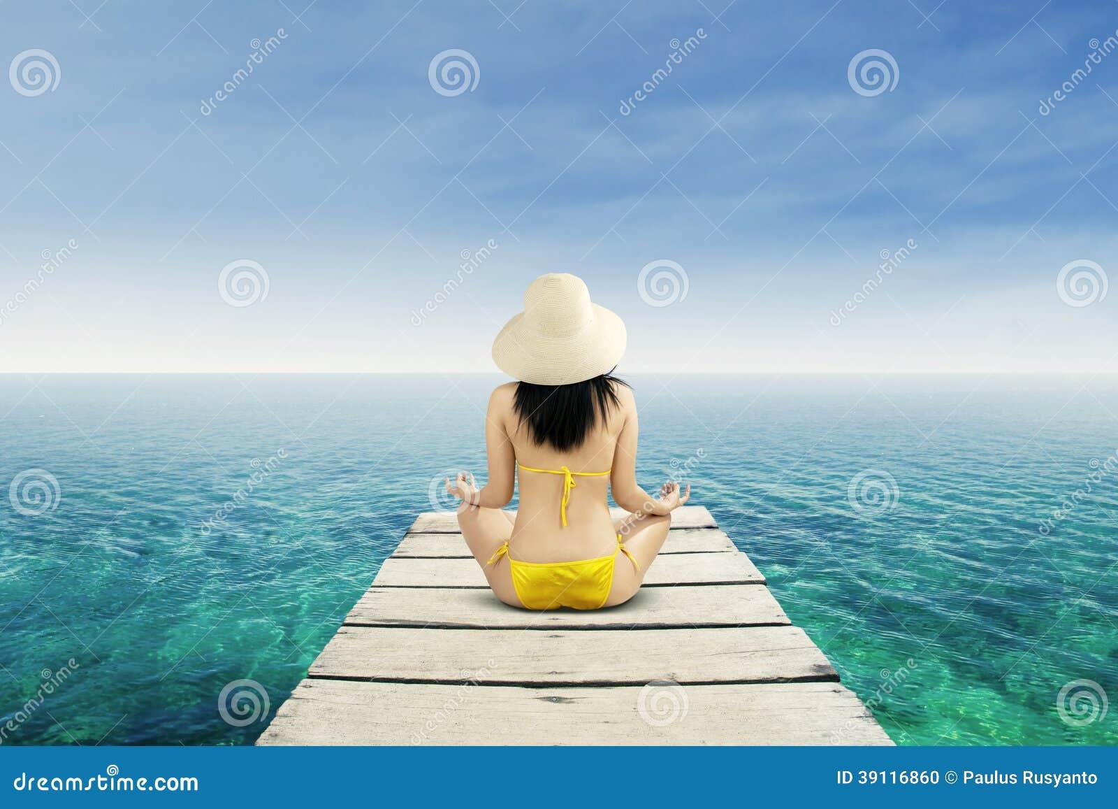 Vrouw die bij rustig strand mediteren