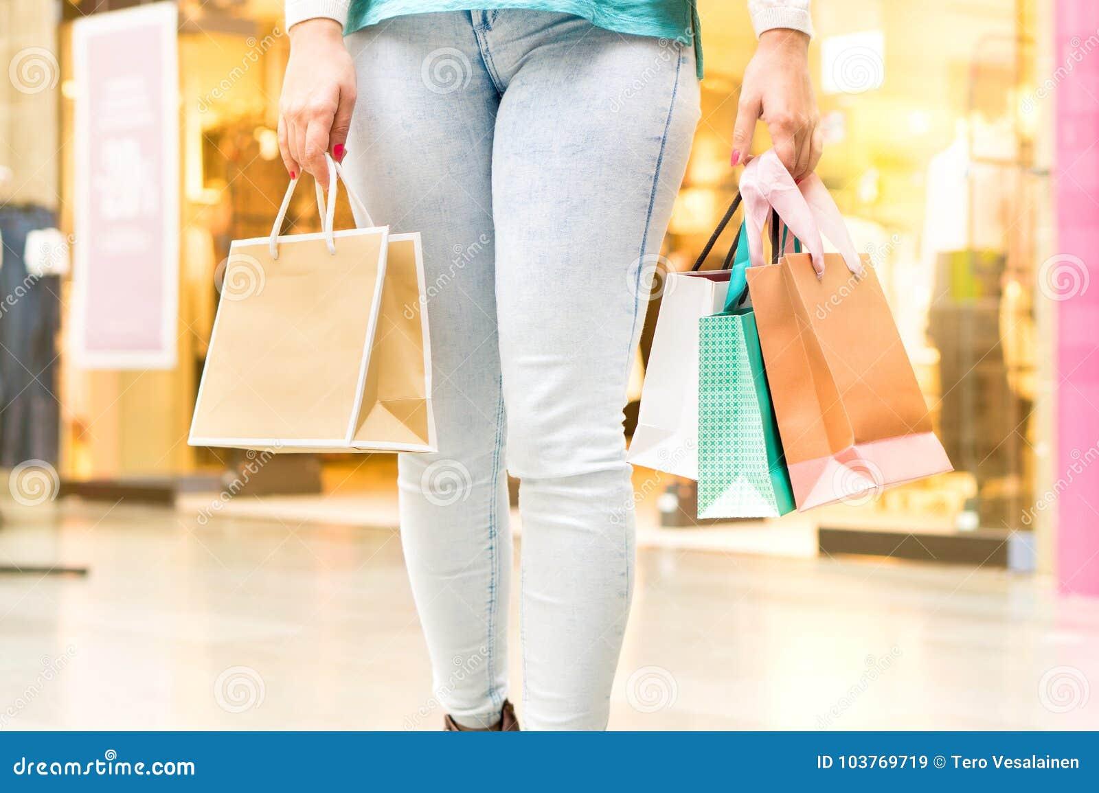Vrouw die bij wandelgalerij dragende het winkelen zakken lopen
