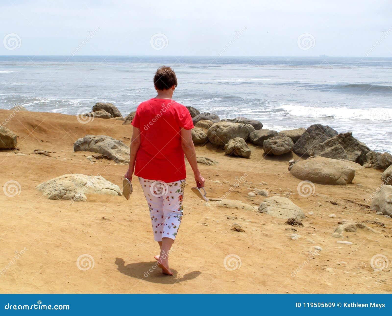 Vrouw die blootvoets op Oceaanstrand lopen