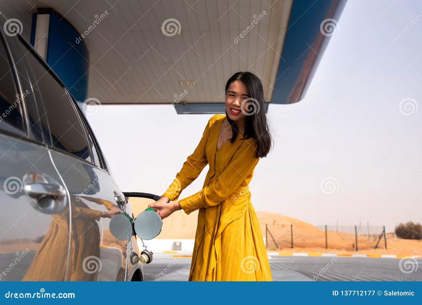 Vrouw die brandstof op het benzinestation toevoegen