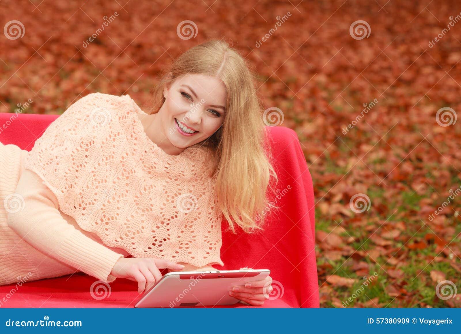 Vrouw die in dalingspark met tablet Internet doorbladeren
