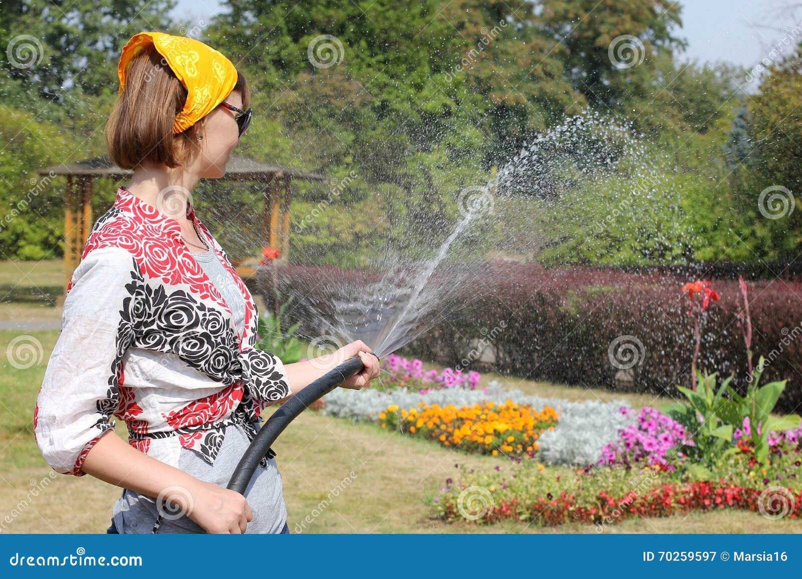 Vrouw die de bloemen water geeft