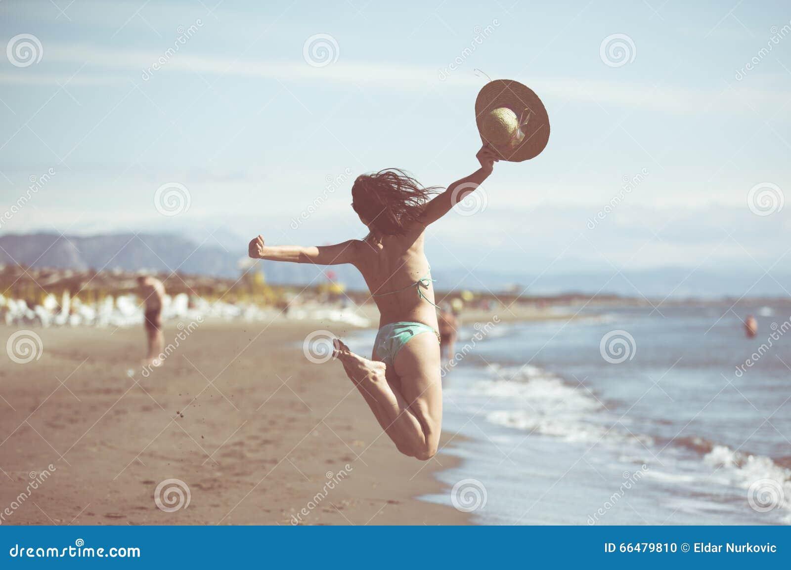 Vrouw die in de lucht op tropisch strand springen, pret hebben en de zomer, het mooie speelse vrouw springen vieren van geluk