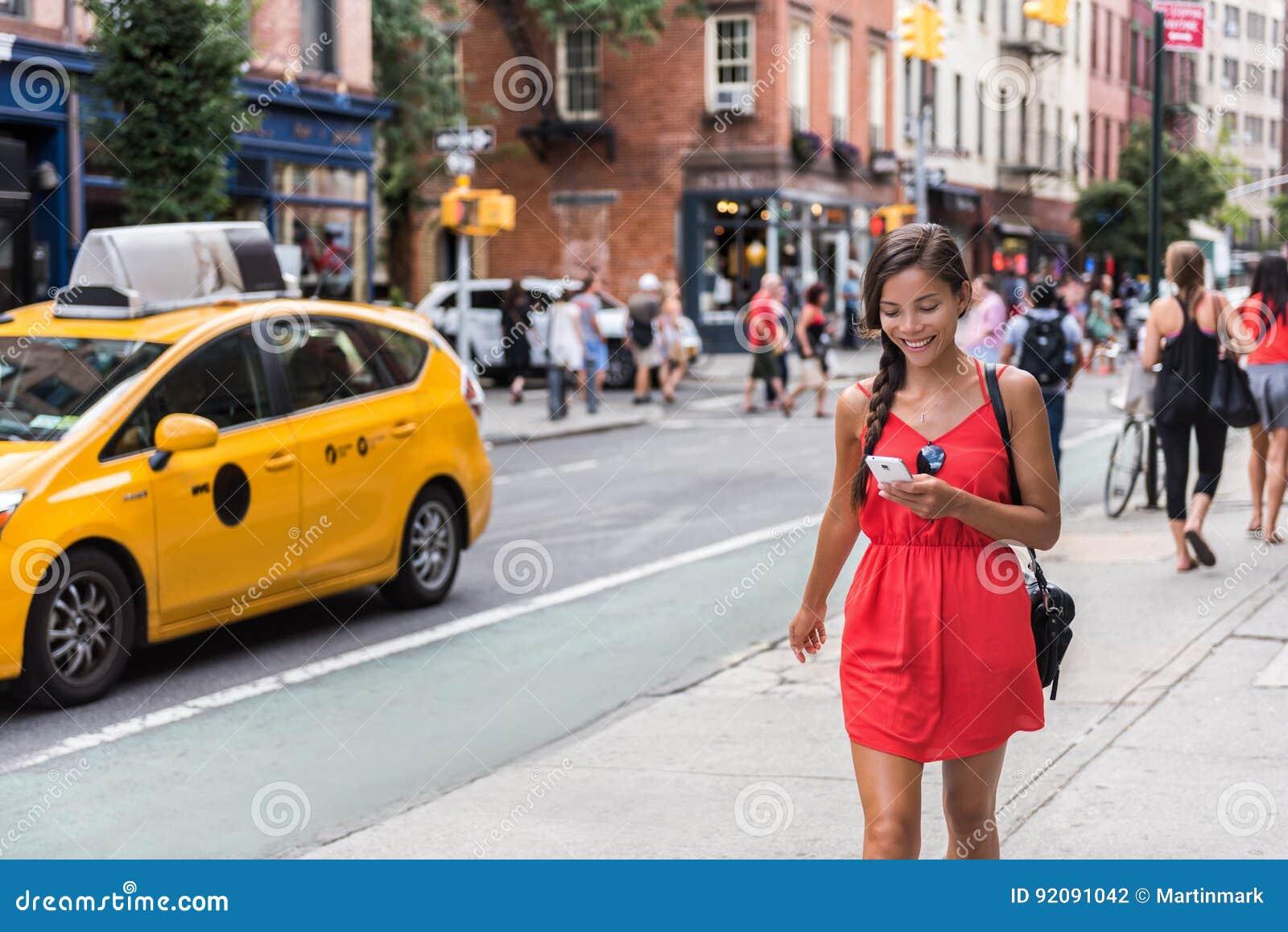 Vrouw die in de stad die van New York lopen telefoon app met behulp van
