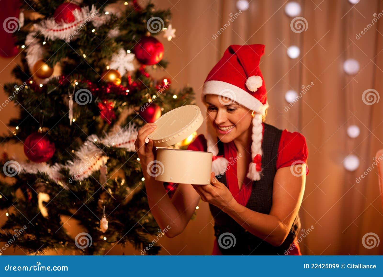 Vrouw die dichtbij Kerstboom binnengift kijkt