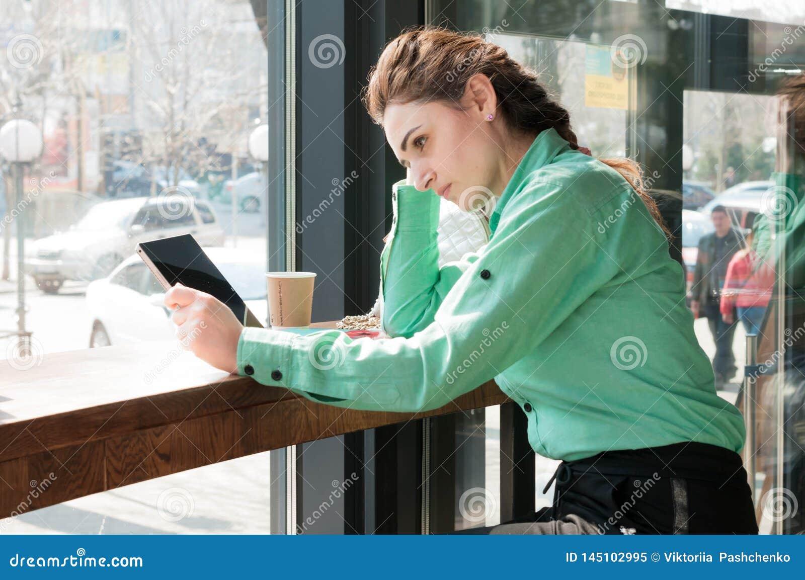 Vrouw die digitale tablet met het lege scherm in koffiewinkel bekijken