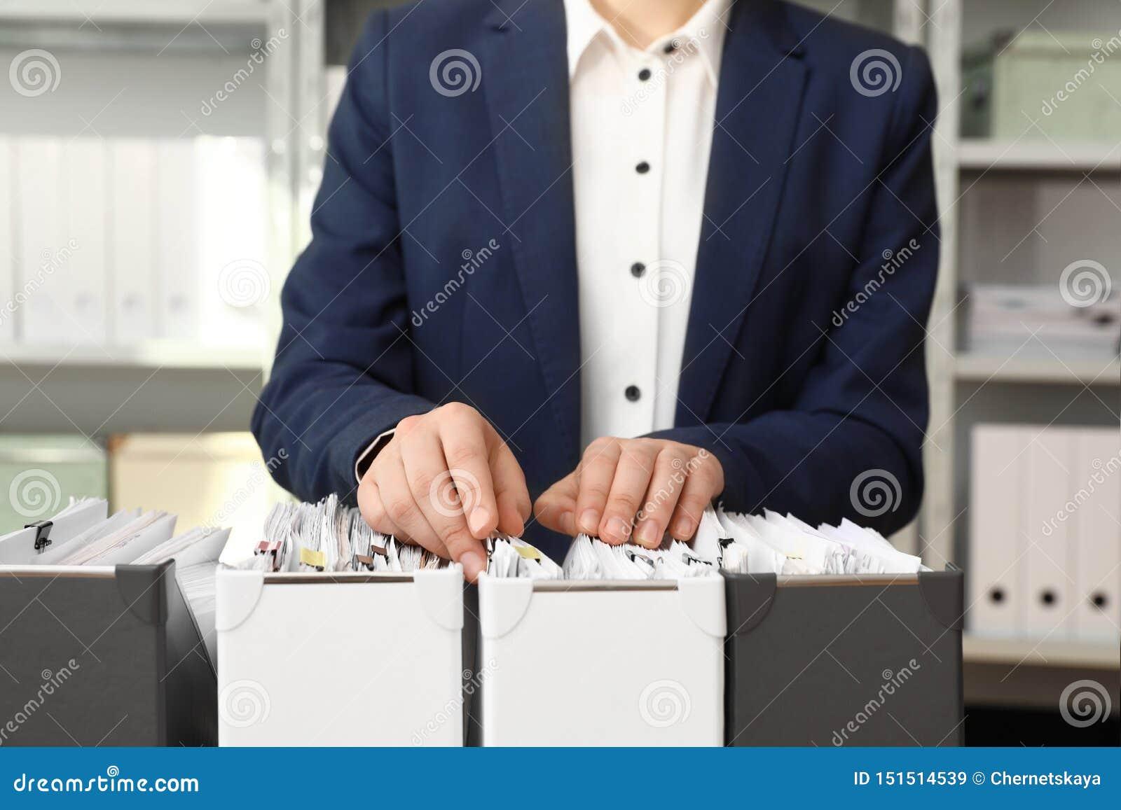Vrouw die documenten van omslag in archief nemen