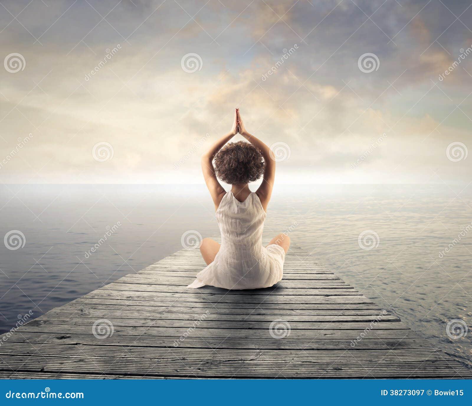 Vrouw die doend yoga ontspannen