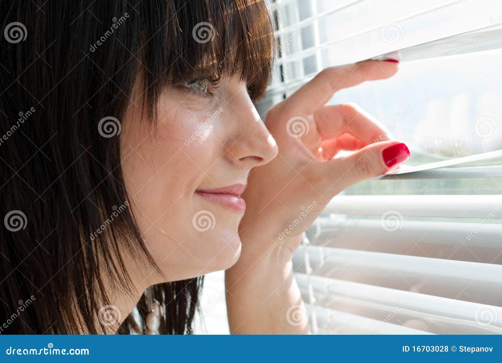 Vrouw die door jaloezie kijkt