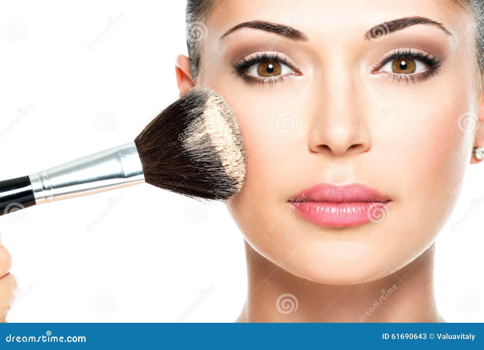 Vrouw die droge kosmetische toon- stichting op het gezicht toepassen