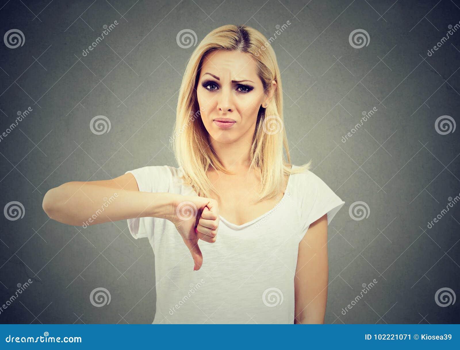 Vrouw die duim onderaan gebaar geven die met negatieve uitdrukking en afkeuring kijken