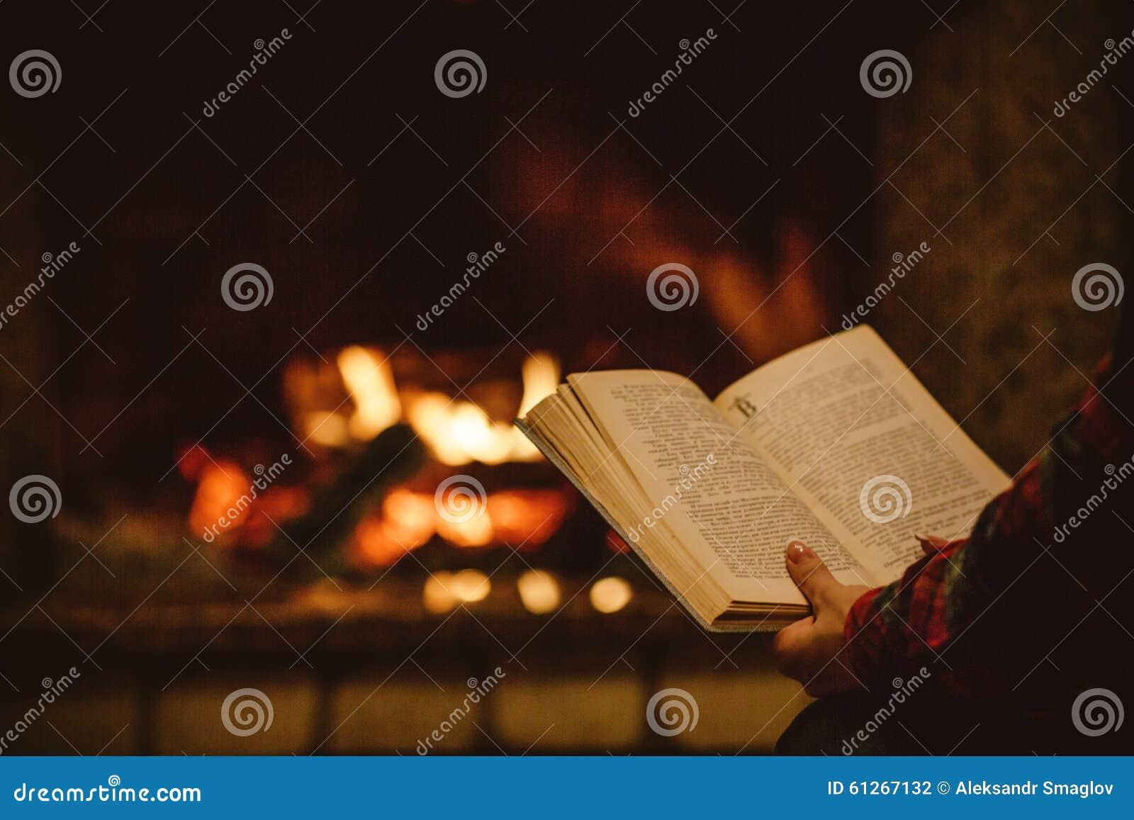 Vrouw die een boek lezen door de open haard Jonge vrouw die een boek leest