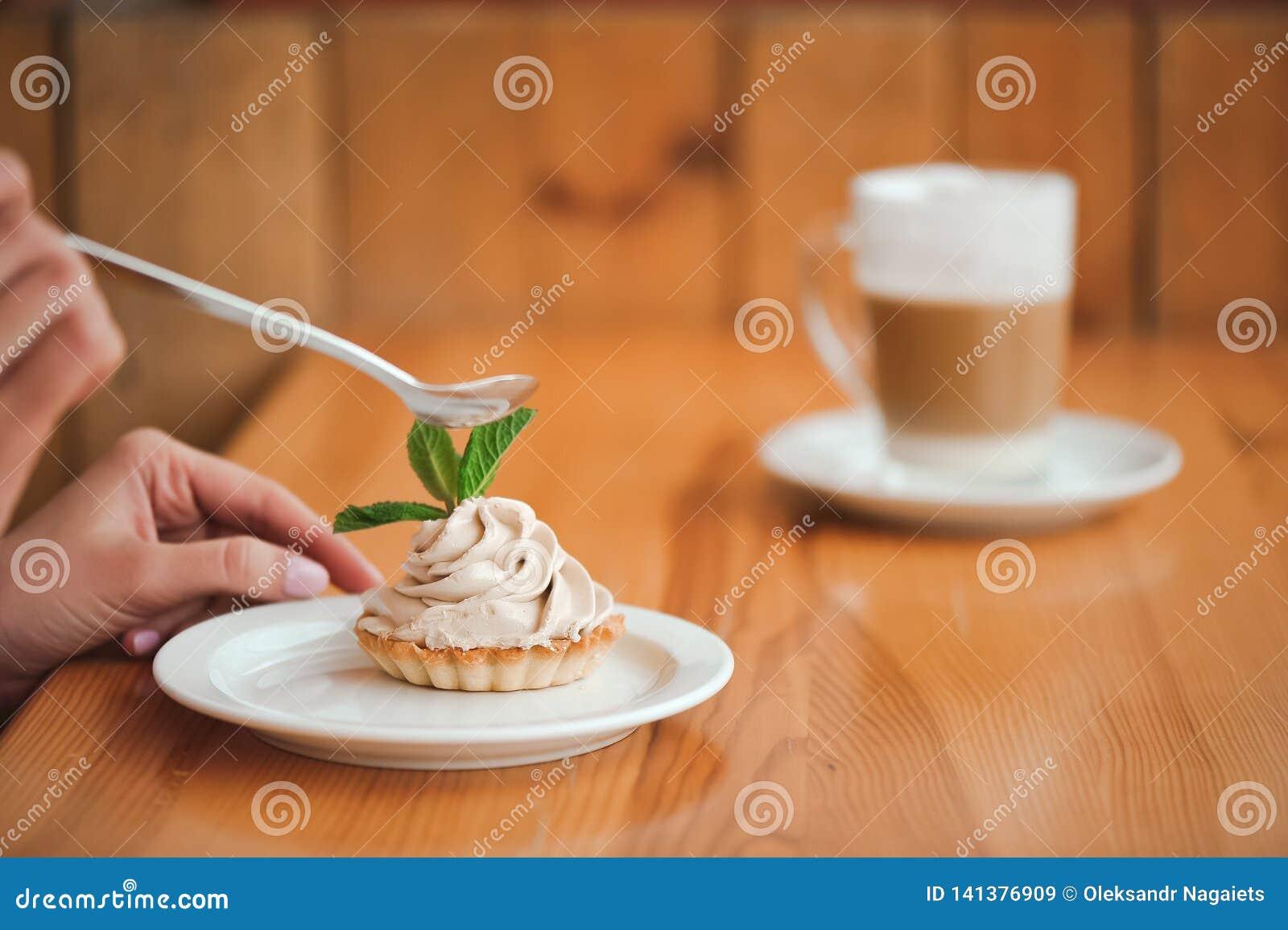 Vrouw die een cake van kwark in een ceramische plaat met een lepel op een houten lijst eten