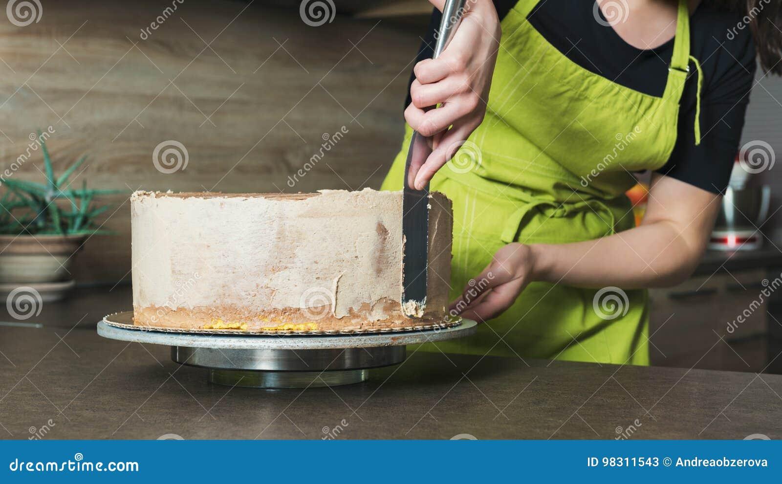 Vrouw die een heerlijk gelaagd biscuitgebak met de room van het chocoladesuikerglazuur verfraaien