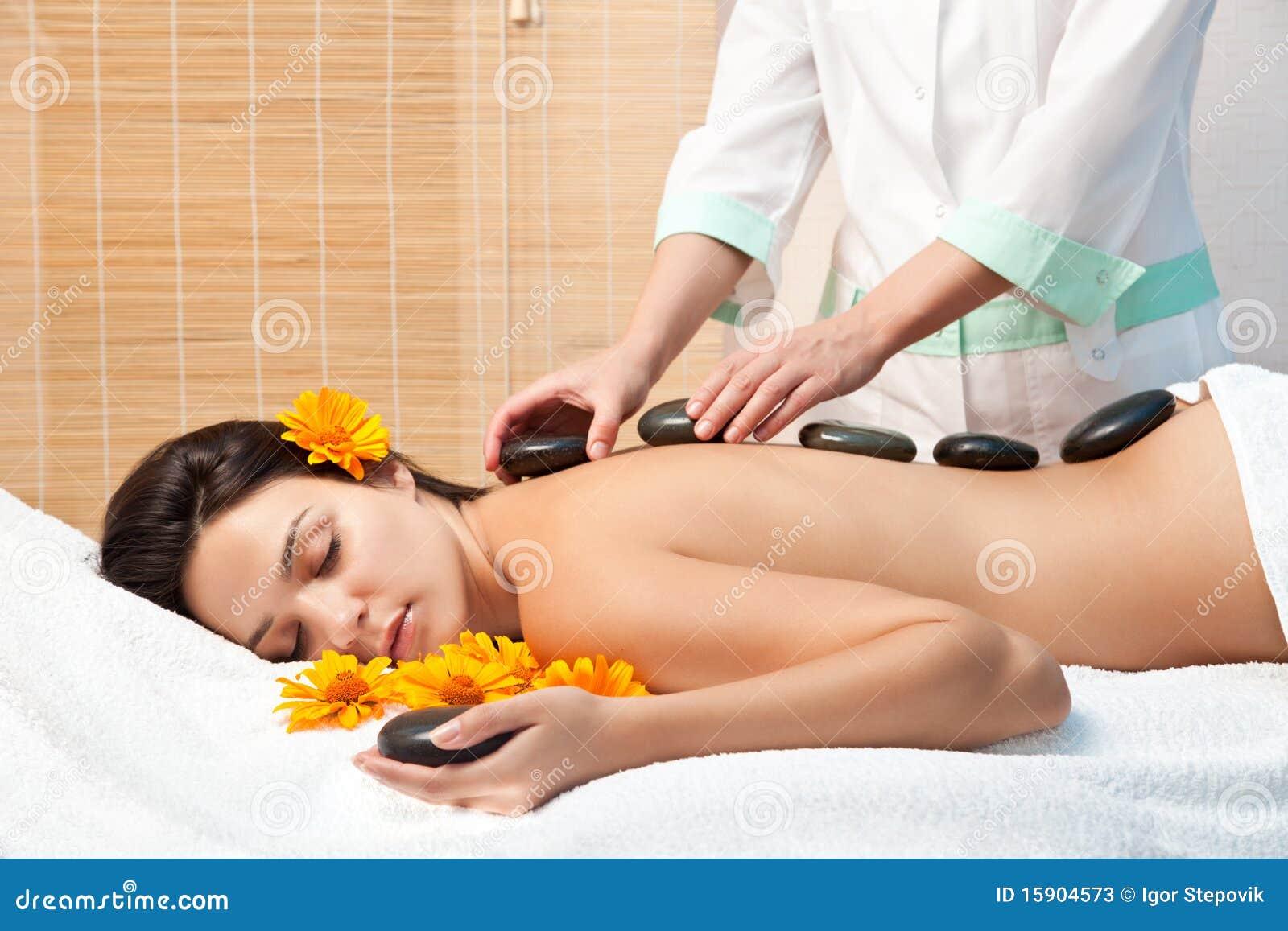 Vrouw die een hete steenmassage krijgt bij kuuroordsalon