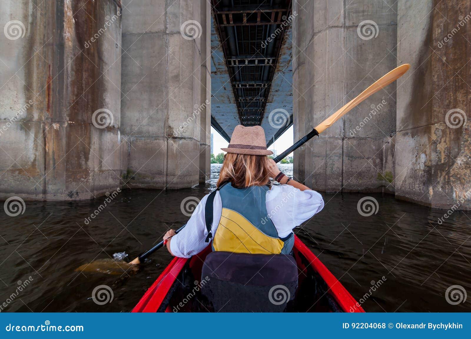 Vrouw die een kajak in de rivier tussen brugsteunen paddelen Kayaking in de stad Het stedelijke concept van het de zomeravontuur