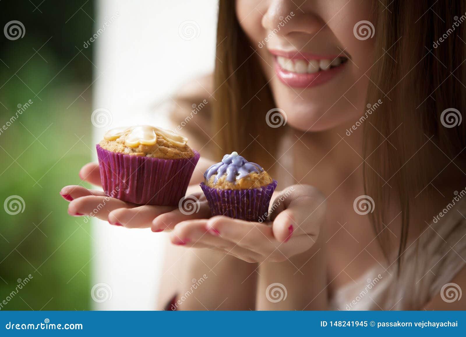 Vrouw die een kopcake houden