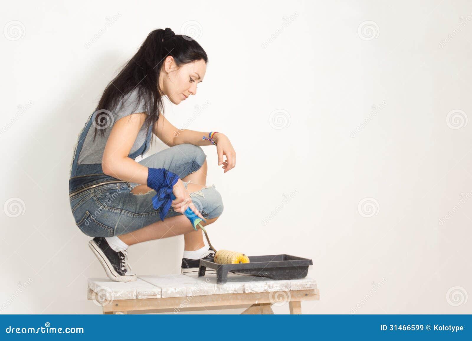 Vrouw die een rol met behulp van om een muur te schilderen