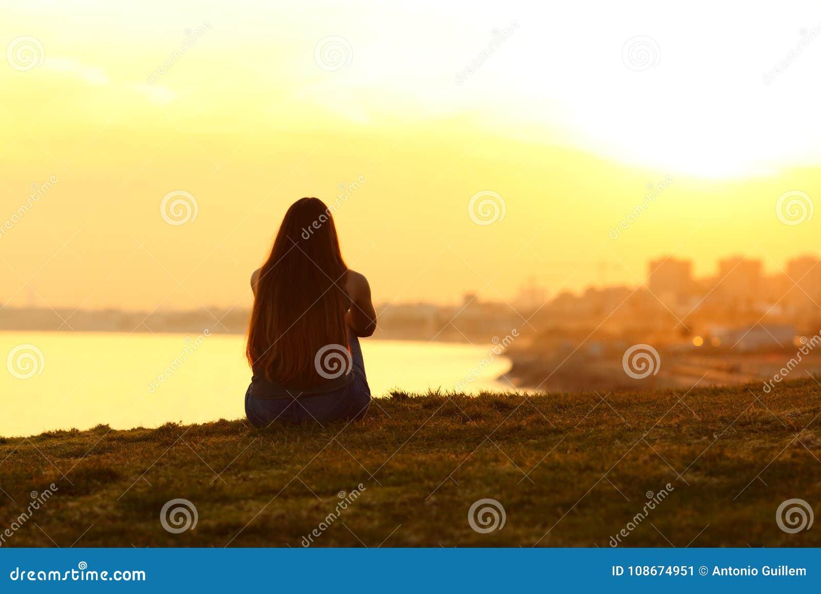 Vrouw die een zonsondergang op de stad zien