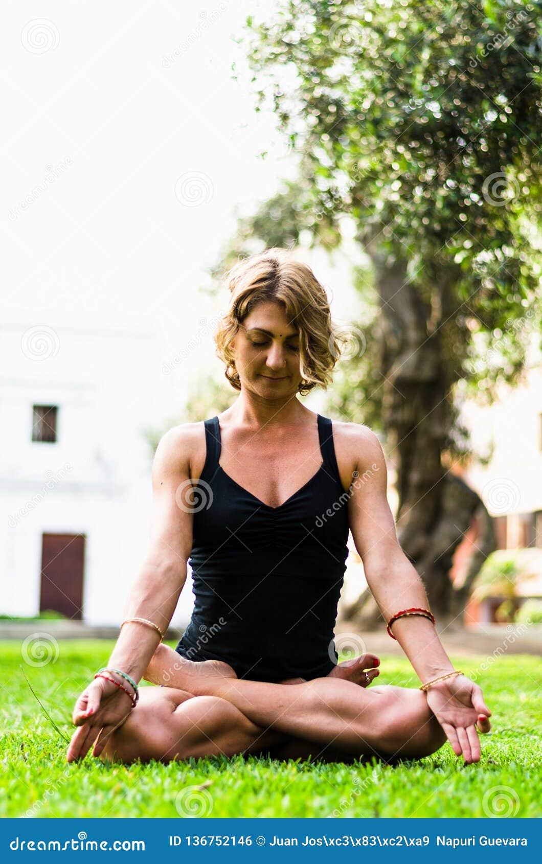 Vrouw die en het Praktizeren Yoga, Padmasana mediteren Meditatie op Sunny Autumn Day At Park Training Openlucht