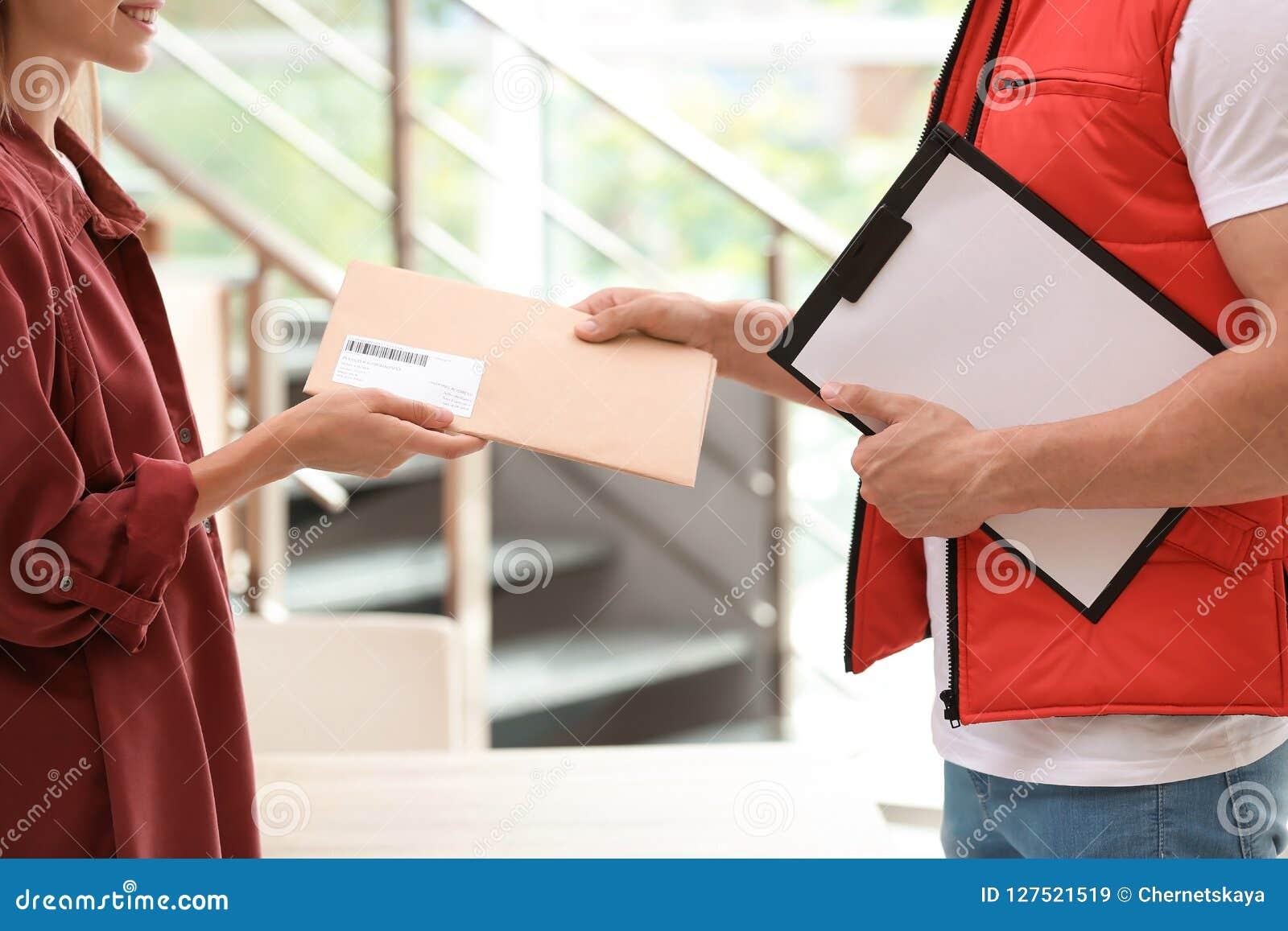 Vrouw die envelop van de koerier van de leveringsdienst ontvangen