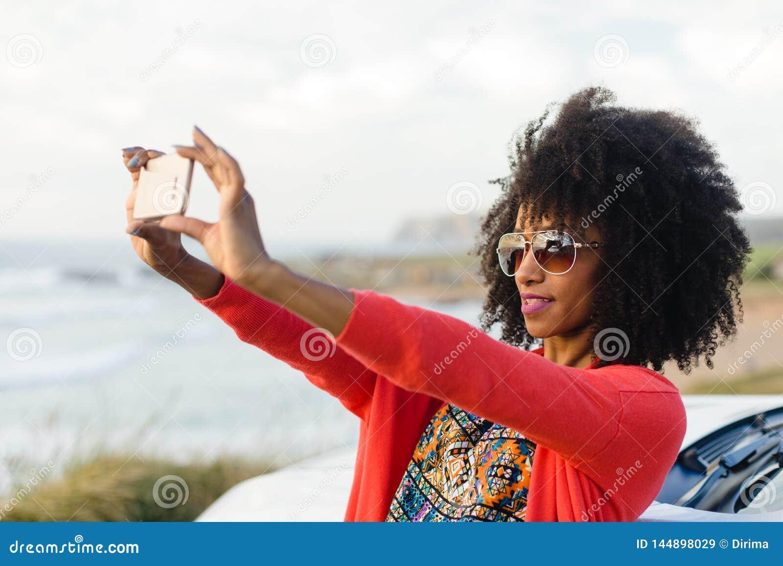 Vrouw die foto met mobiele telefoon nemen tegen het overzees