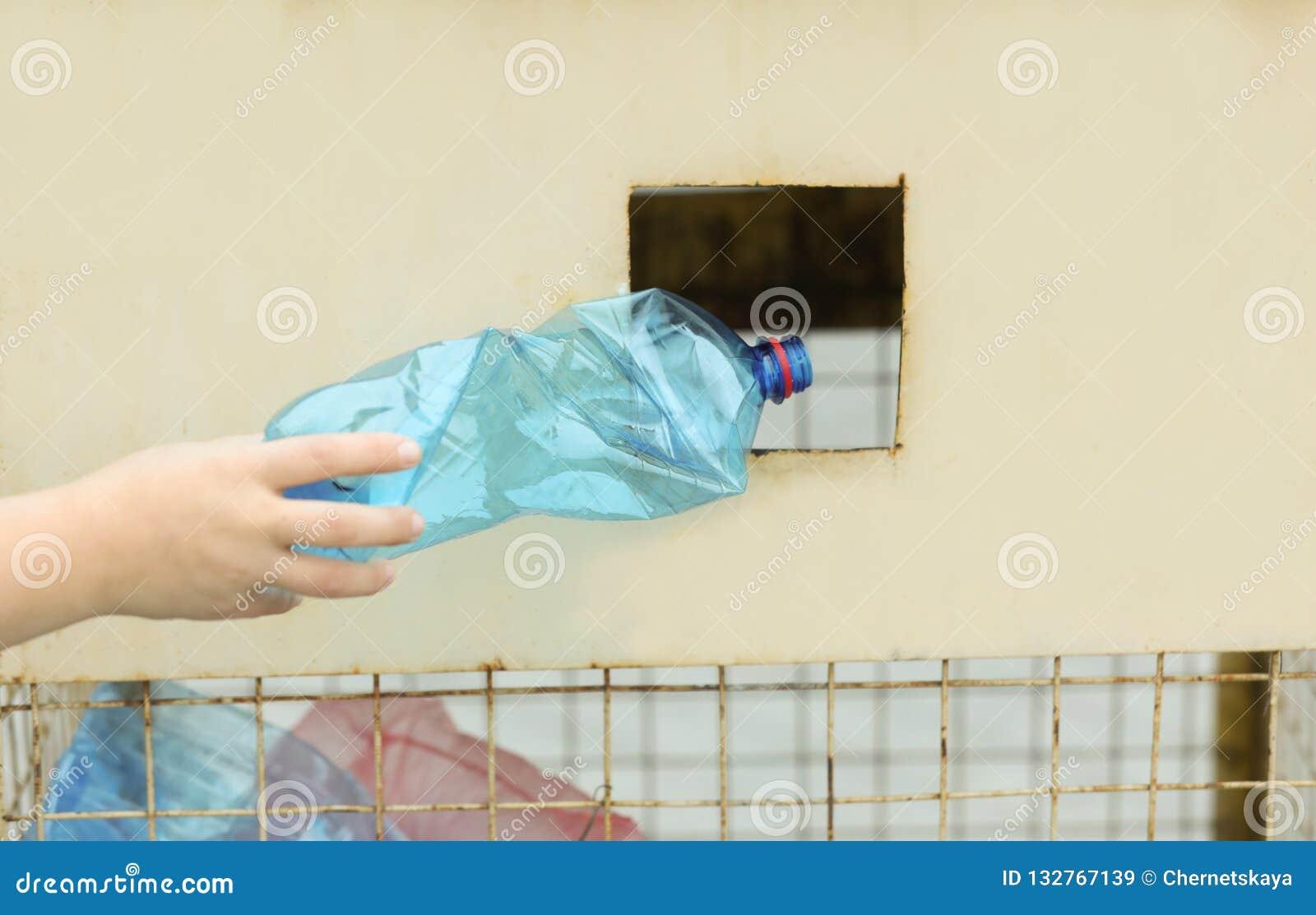 Vrouw die gebruikte plastic fles werpen in het recycling van bak op straat