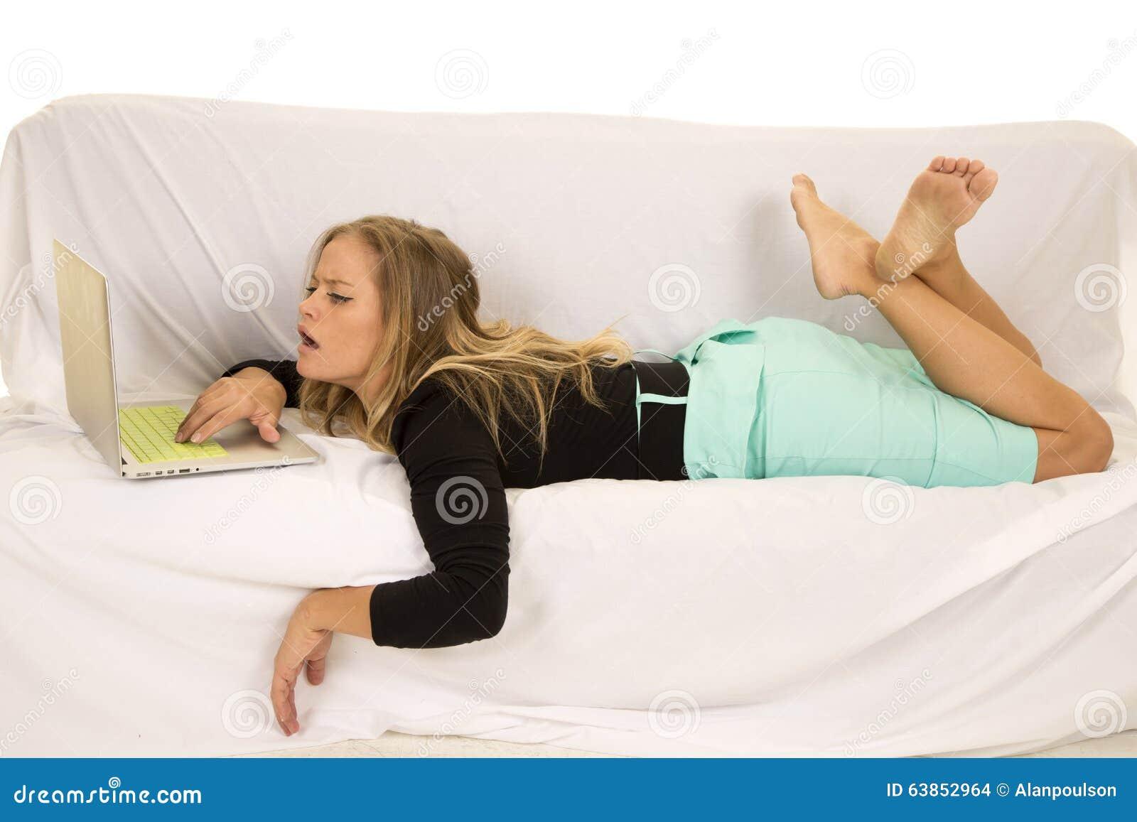 Vrouw die in groene rok met laptop de leggen bekijkt het scherm